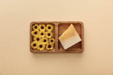 Photo for Top view of brown wooden soapdish with flowers and piece of soap on beige background - Royalty Free Image