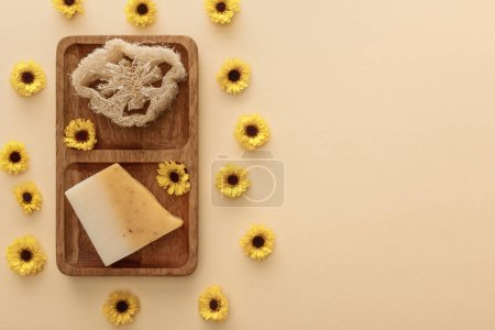 Photo for Top view of brown wooden soapdish with loofah and piece of soap on beige background with flowers - Royalty Free Image