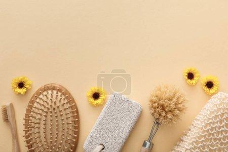 Photo pour Vue de dessus de brosse à dents, brosse à cheveux, brosse à corps, éponge de bain et pierre ponce sur fond beige avec des fleurs - image libre de droit