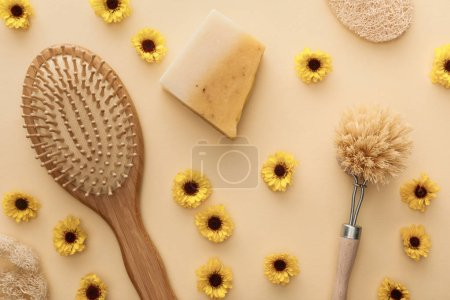Photo for Top view of hairbrush, body brush, loofah and piece of soap on beige background with flowers - Royalty Free Image