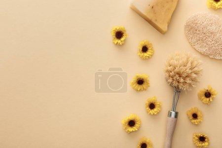 Photo pour Vue du haut de la brosse pour le corps, loofah et morceau de savon sur fond beige avec fleurs et espace de copie - image libre de droit