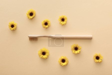 Photo for Top view of toothbrush on beige background with flowers - Royalty Free Image