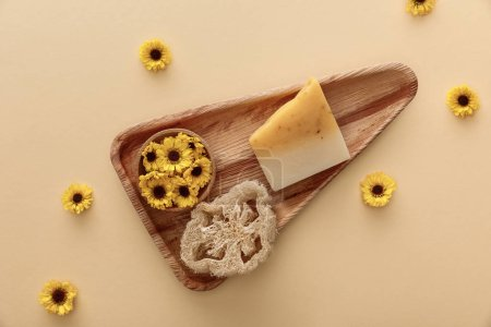 Photo for Top view of triangle wooden dish with soap, loofah and flowers on beige background - Royalty Free Image