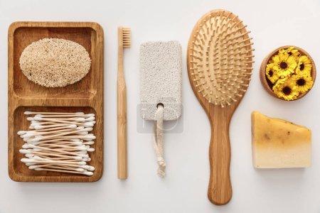 Photo pour Plat lay avec le plat en bois avec des écouvillons de coton et le loofah près de la brosse à dents, de la brosse à cheveux, du morceau de savon, de la pierre ponce et de la tasse avec des fleurs sur le fond blanc - image libre de droit