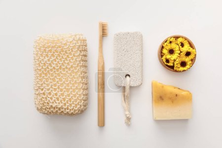 Photo pour Plat lay avec l'éponge de bain près de la brosse à dents, morceau de savon, pierre ponce et tasse avec des fleurs sur le fond blanc - image libre de droit