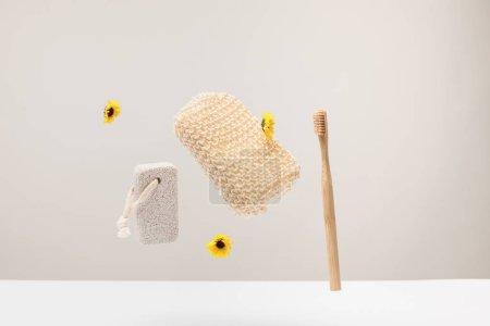 Photo pour Brosse à dents, pierre ponce, éponge de bain et fleurs isolées sur gris - image libre de droit