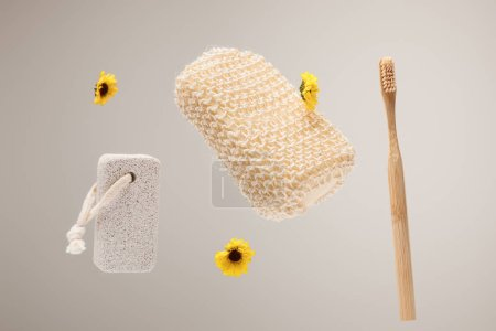Photo for Toothbrush, pumice stone, bath sponge and yellow flowers isolated on gray - Royalty Free Image