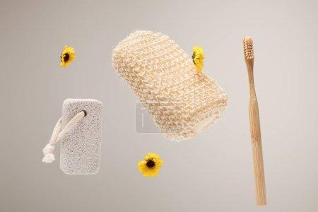 Foto de Cepillo de dientes, piedra pómez, esponja de baño y flores amarillas aisladas en gris - Imagen libre de derechos