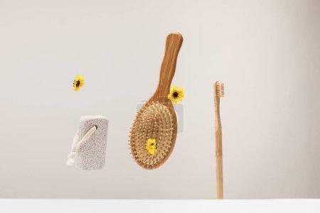 Photo pour Brosse à dents, pierre ponce, brosse à cheveux et fleurs isolées sur gris - image libre de droit