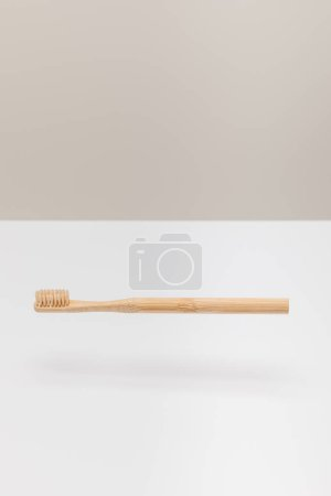 Photo for Natural wooden toothbrush above white surface isolated on gray - Royalty Free Image