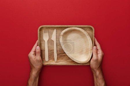 Photo pour Vue recadrée de l'homme tenant plat rectangulaire naturel en bois avec plaque, fourchette et couteau sur fond rouge - image libre de droit