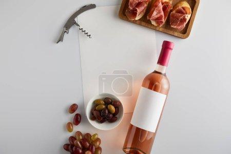Photo pour Vue du dessus de la bouteille avec vin rose près du raisin, tire-bouchon, olives, papier blanc et prosciutto tranché sur baguette sur fond blanc - image libre de droit