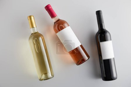 Photo for Top view of bottles with white, rose and red wine on white background - Royalty Free Image