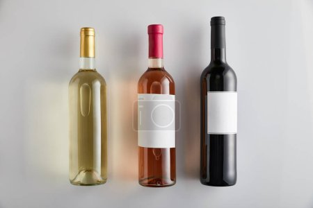 Photo for Flat lay with bottles with white, rose and red wine on white background - Royalty Free Image