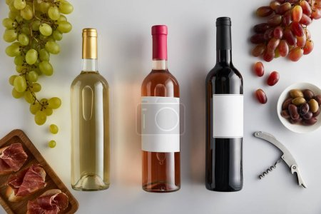 Photo for Top view of bottles with white, rose and red wine near grape, corkscrew, olives and sliced prosciutto on baguette on white background - Royalty Free Image