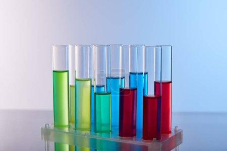 Photo pour Tubes à essai en verre avec liquide coloré sur fond bleu - image libre de droit