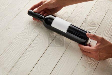 Photo pour Vue recadrée de l'homme tenant une bouteille de vin avec une étiquette vierge sur une surface en bois blanc - image libre de droit