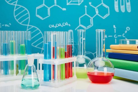books, glass test tubes and flasks with colorful liquid on blue background with molecular structure