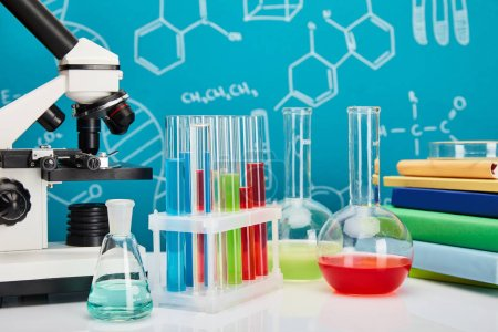 microscope, books, glass test tubes and flasks with colorful liquid on blue background with molecular structure