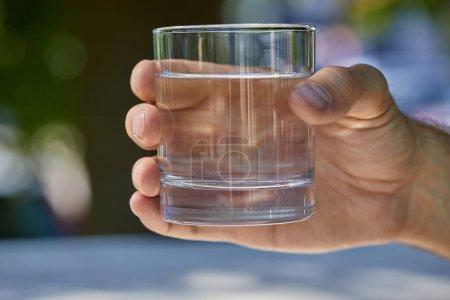 Photo pour Vue recadrée de l'homme tenant le verre avec de l'eau douce claire extérieure - image libre de droit