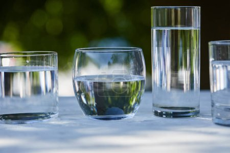 Photo pour Clear fresh water in transparent glasses in sunlight on wooden table - image libre de droit