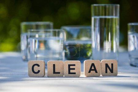 Photo pour Lettrage propre sur les blocs près de l'eau douce dans des verres transparents à la lumière du soleil sur une table en bois - image libre de droit