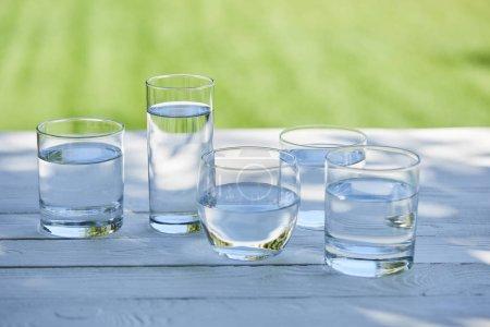 Photo pour Eau douce claire dans des verres transparents à la lumière du soleil sur une table en bois - image libre de droit