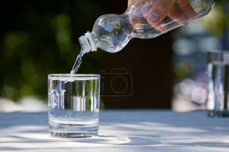 Photo for Cropped view of man pouring clean water from plastic bottle into glass - Royalty Free Image