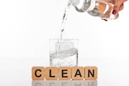 Photo pour Vue recadrée de la femme versant de l'eau de bouteille en verre près de cubes avec lettrage propre isolé sur blanc - image libre de droit