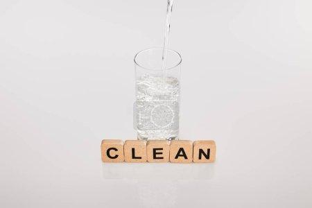 Photo pour Eau douce claire versant dans du verre près de cubes avec un lettrage propre sur fond gris - image libre de droit