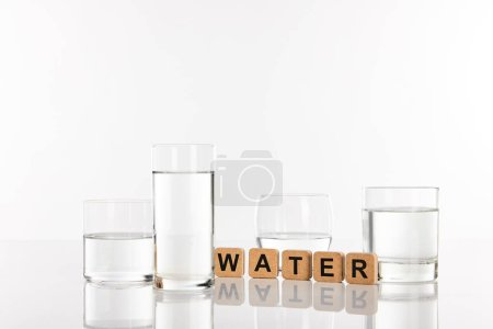 Photo pour Clear fresh water in glasses near cubes with water lettering isolated on white - image libre de droit