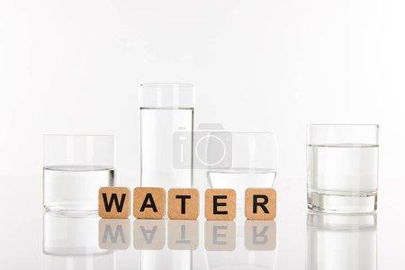 Photo pour Eau douce claire dans des verres près de cubes avec lettrage d'eau isolé sur blanc - image libre de droit
