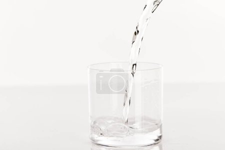 clear fresh water pouring into glass isolated on white