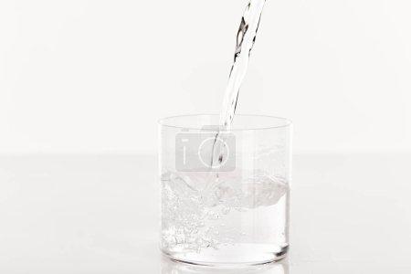 Photo pour Eau douce limpide coulée dans du verre isolée sur du - image libre de droit