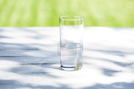 Photo pour Eau fraîche et propre en verre transparent à la journée ensoleillée sur table en bois - image libre de droit