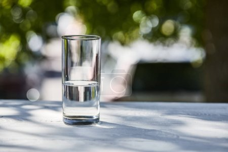 Photo for Fresh clean water in transparent glass at sunny day outside on wooden table - Royalty Free Image