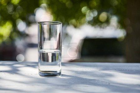 Photo pour De l'eau fraîche et propre dans un verre transparent au soleil sur une table en bois - image libre de droit