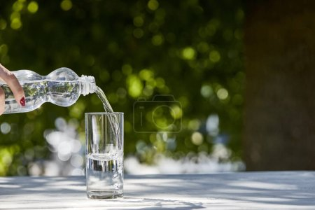 Photo for Cropped view of woman pouring fresh clean water from bottle in transparent glass at sunny day on wooden table - Royalty Free Image