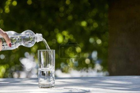 Photo pour Vue recadrée de la femme versant de l'eau fraîche et propre de la bouteille en verre transparent à la journée ensoleillée sur une table en bois - image libre de droit