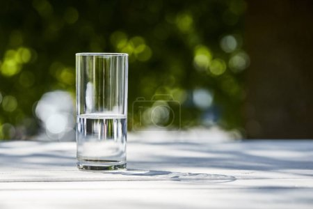 Photo pour Fresh clean water in transparent glass at sunny day outside on wooden table - image libre de droit