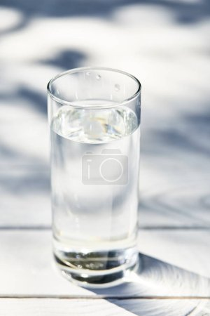 fresh clean water in transparent glass at sunny day on white wooden table