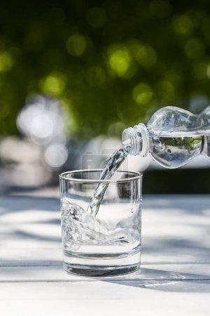 Photo for Fresh clean water pouring from bottle in transparent glass at sunny day on wooden table - Royalty Free Image