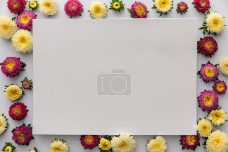 Foto de Top view of yellow and purple asters and blank paper on white background - Imagen libre de derechos