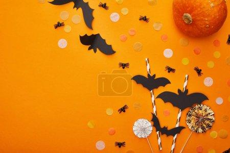 Photo pour Top view of pumpkin, bats and spiders with confetti on orange background, Halloween decoration - image libre de droit
