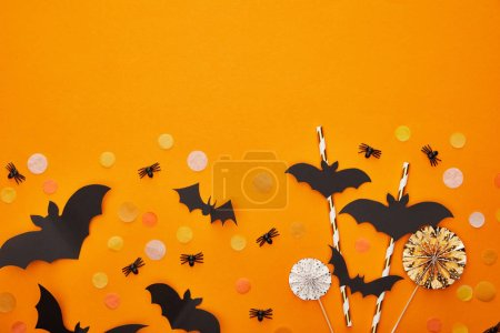 Photo pour Top view of bats and spiders with confetti on orange background, Halloween decoration - image libre de droit