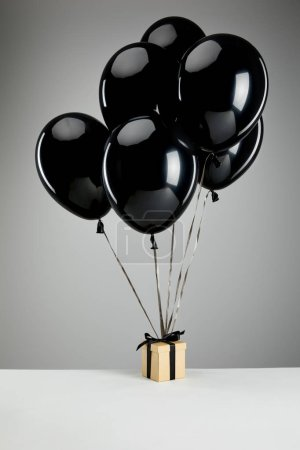 Photo for Bunch of black balloons with gift box isolated on grey, black Friday concept - Royalty Free Image