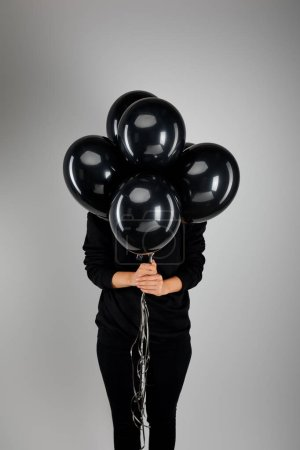 Photo for Woman with obscure face holding bunch of black balloons isolated on grey, black Friday concept - Royalty Free Image