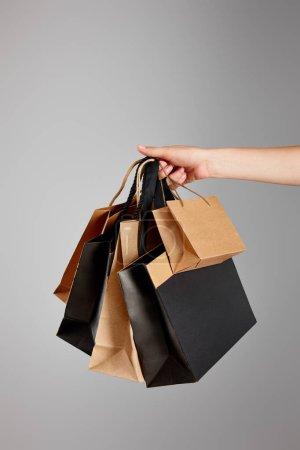 Photo pour Vue partielle d'une femme tenant un sac en papier isolé sur fond gris et noir Concept du vendredi - image libre de droit