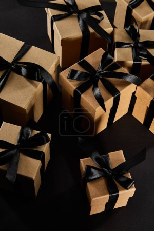 Photo for Cardboard gift boxes with black ribbons isolated on black, black Friday concept - Royalty Free Image