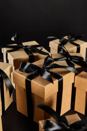 Photo for Selective focus of cardboard gift boxes with black ribbons isolated on black, black Friday concept - Royalty Free Image